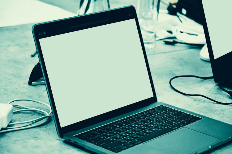 Open laptop computer with blank white screen Technology Wireless Technology Laptop Connection Communication Computer Table Keyboard Blank Device Screen Focus On Foreground Computer Equipment Screen Still Life Portable Information Device Close-up Indoors  No People Desk Working Modern Working Place Working Environment Office Copy Space