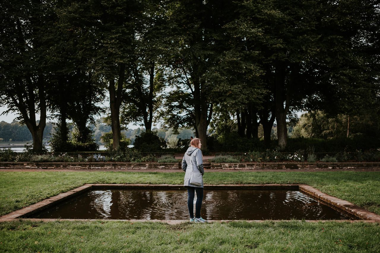 Woman standing by pond at park