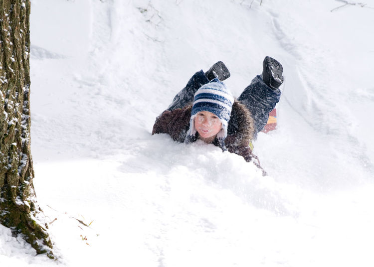Young boy playing outdoors on a toboggan Activity Adventure Boy Child Childhood Cold Temperature Day Fun Fun Happiness Hill Leisure Activity Motion Outdoor Activity Outdoors People Play Recreational Pursuit Sled Sledding Sledding Hill Snow Tobogganing Warm Clothing Winter