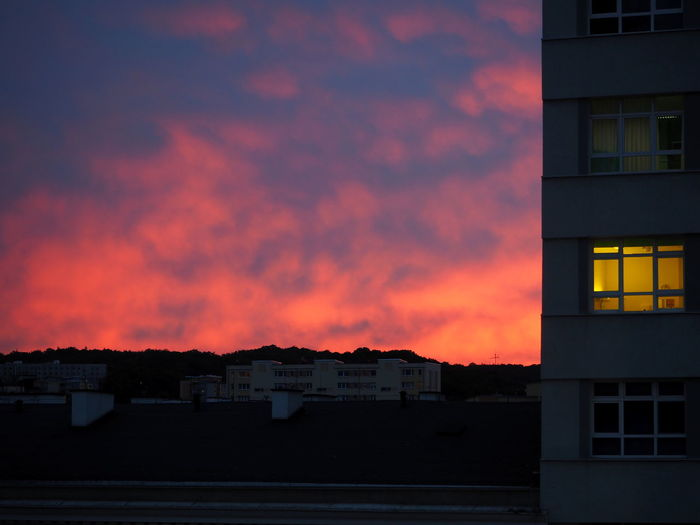 Houses against sky during sunset