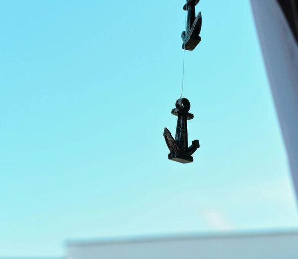 Low angle view of anchors hanging against clear blue sky
