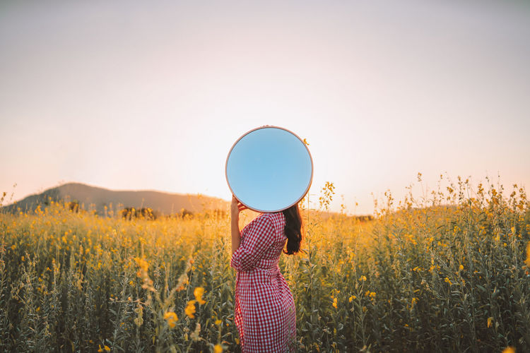 Woman holding mirror against face while standing outdoors
