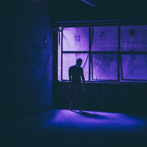 Silhouette man standing in illuminated room