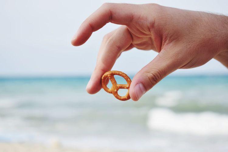 Close-up of hand holding pretzel