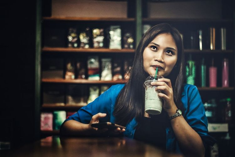 Happy Woman Drinking Coffee While Looking Away At Restaurant
