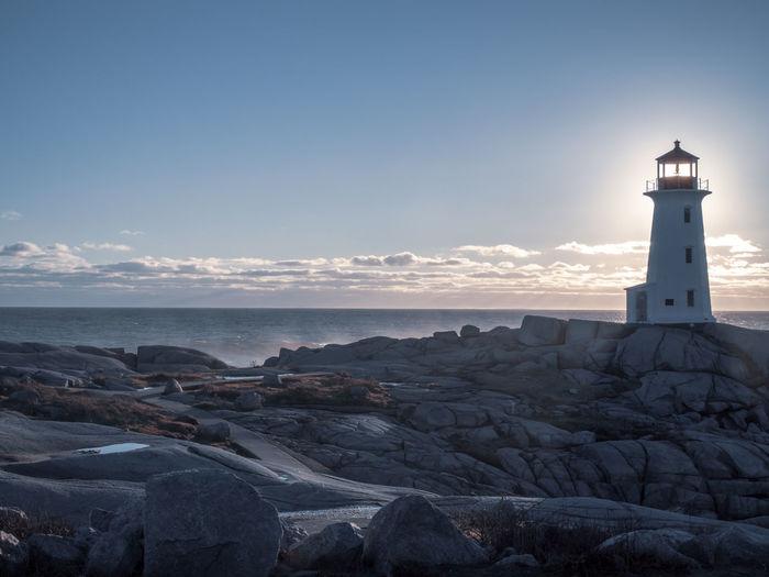 Lighthouse Amidst Buildings And Sea Against Sky