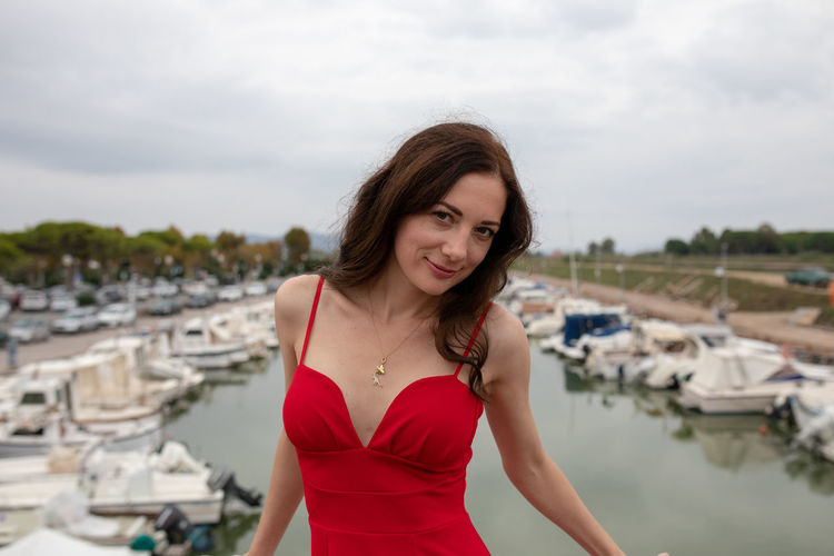 Portrait of woman in red dress standing against harbor in city