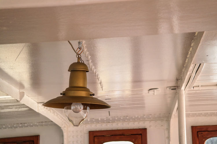 Low angle view of pendant lights hanging from ceiling of building