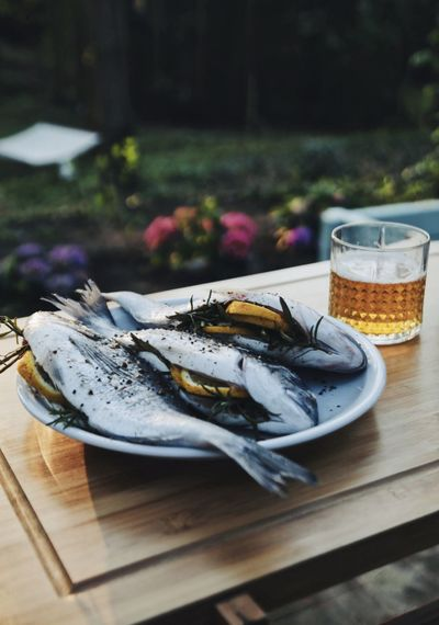 Delicious fishes filled with lemin and rosemary next to a glass of beer