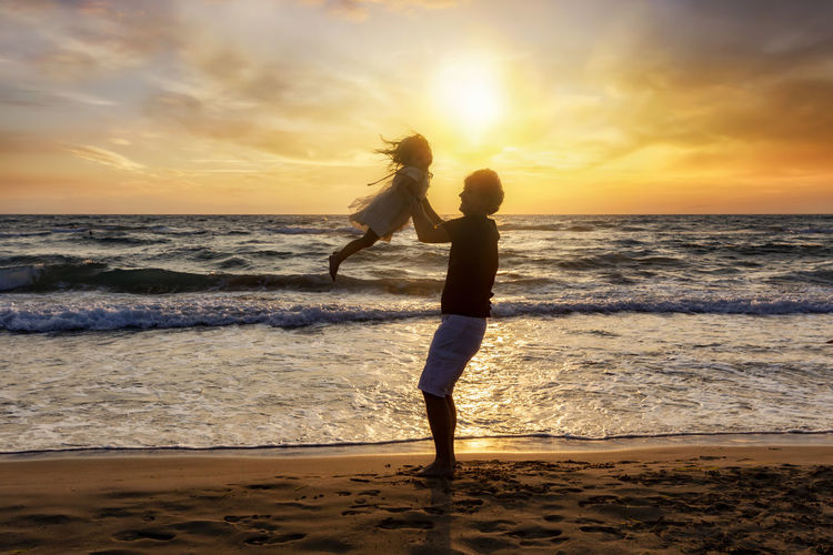 Father and daughter having fun on the beach during sunset time Sea Beach Sky Sunset Water Horizon Over Water Scenics - Nature Two People Cloud - Sky Lifestyles Leisure Activity Positive Emotion Outdoors Motion Daughter Father Holding Family Vacation Silhouette Happiness Playing Fun Love Freedom