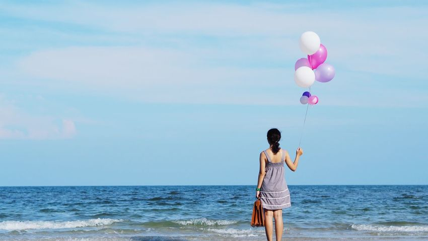 Woman holding vintage luggage beautiful balloons over clearly blue sky background.freedom from travel concept Travel Vintage Luggage Balloon Balloons Beach Beauty In Nature Day Flying Helium Balloon Holding Horizon Over Water Leisure Activity Lifestyles Mid-air Nature One Person Outdoors People Real People Rear View Scenics Sea Sky Standing Young Adult