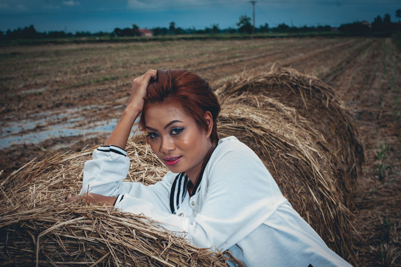 Portrait of woman sitting on hay bale at field