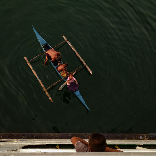 High angle view of people sitting on boat in lake