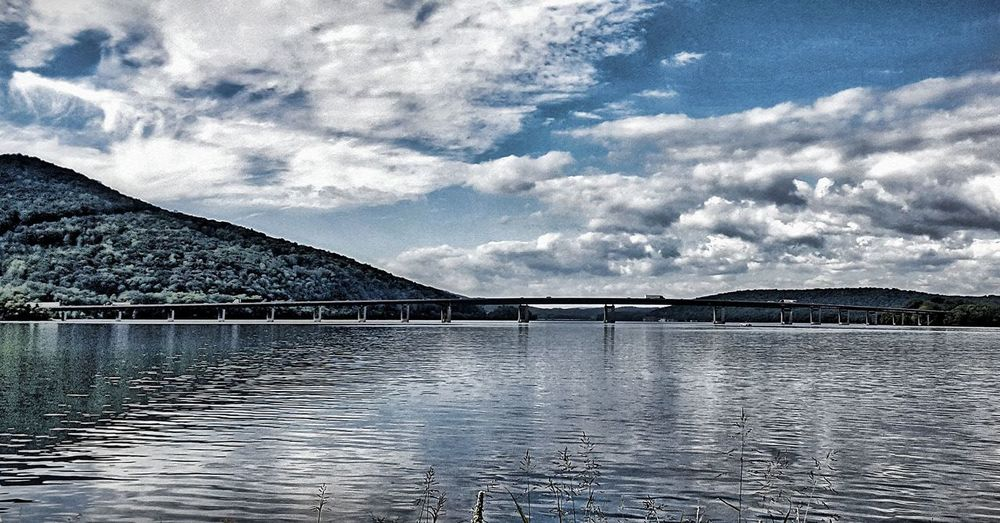 Beauty In Nature Blue Blue Sky Bridge Bridge - Man Made Structure Calm Cloud Cloud - Sky Cloudy Day Engineering Mountain Mountain Range Nature No People Outdoors Scenics Sky Sky And Clouds Sky Lines Sun And Clouds Tranquil Scene Tranquility Water Waterfront
