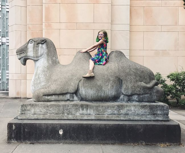 Young Adult Day One Person Young Women Full Length Statue Outdoors Lifestyles Sitting Real People Mammal Animal Themes Camel