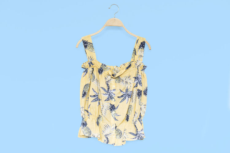 Woman summer blouse with yellow blouse cotton on blue background. Blue Clothing Studio Shot Copy Space Fashion No People Yellow Indoors  Dress Pattern Clear Sky Casual Clothing Cut Out Blue Background Floral Pattern Hanging Still Life Sky Textile Blouse Summer Store Tropical Colorful