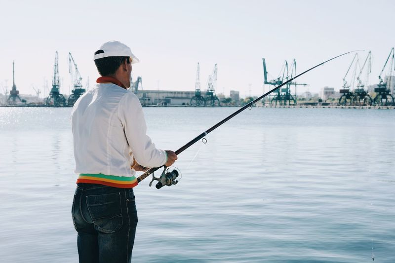 Shipyard Cranes Industrial Fishing Fisherman One Person One Man Only Harbor Harbour Harbour View Water Men Headwear Sea Social Issues Sky Urban Fashion Jungle The Modern Professional 2018 In One Photograph Redefining Menswear