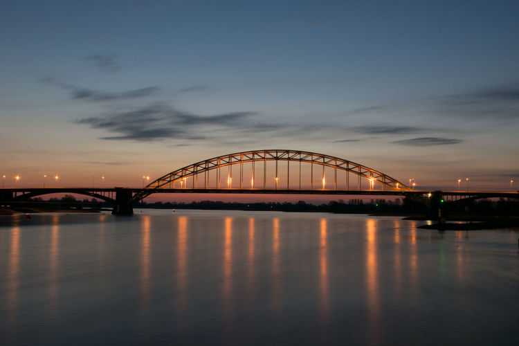 Arch bridge over river against sky at sunset