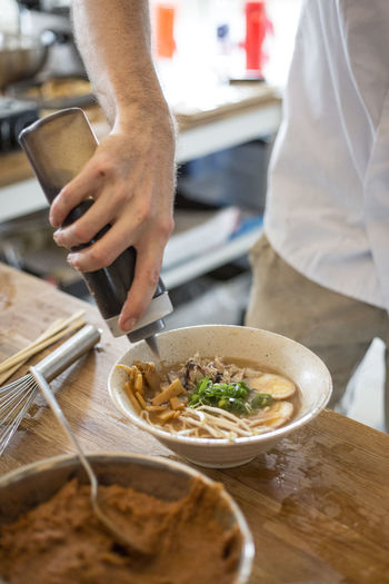Midsection of man pouring sauce in soup bowl