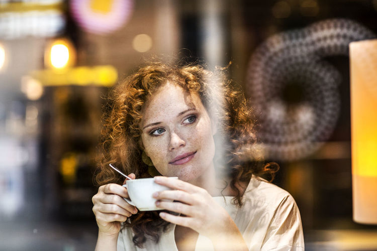Portrait of young woman drinking coffee in cafe