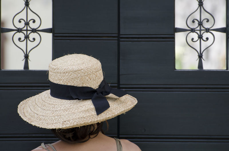 Woman with a straw hat close to a door with small windows. Adults Only Backside Clothes Color Door Fashion Hat Head And Shoulders Headshot Human Body Part Lifestyles One Person One Woman Only Outdoors People Portrait Protection Rear View Retro Styled Simplicity Straw Hat Waiting Window Woman Wood - Material