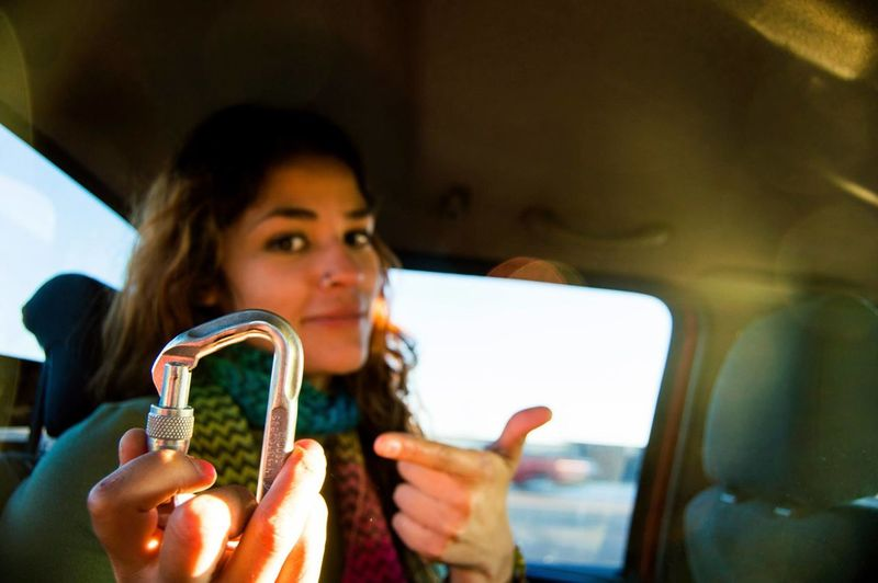 Portrait Of Young Woman Showing Carabiner In Car