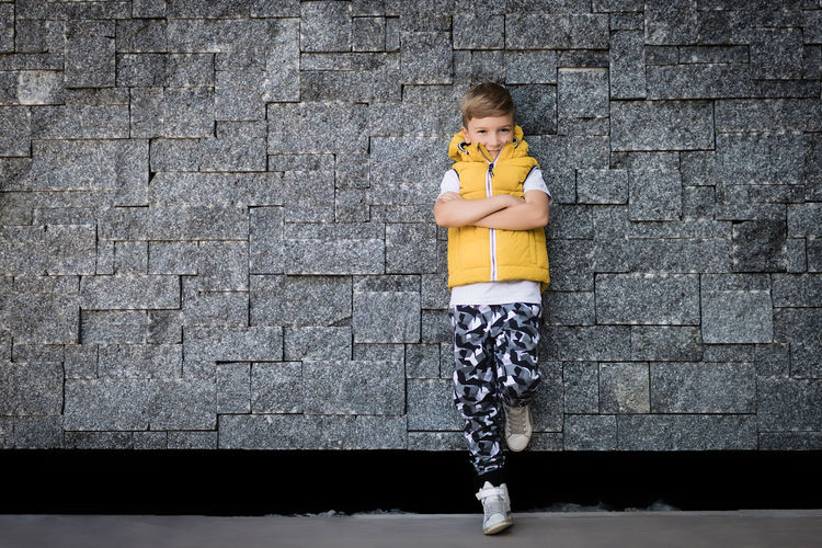 Portrait of boy standing against brick wall