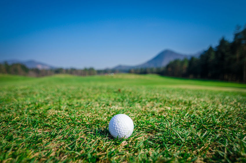 Golf ball on green area with green grass ahead and mountains in background. Nice sunny summer or spring day. Wide angle macro shot. Soft focus or shallow depth of field. Ball Blue Clear Sky Club Golf Golf Golf Ball Golf Ball Golf Club Golf Course Golf Course Golfer Golfing Grass Grass Green Green - Golf Course Leisure Activity Mountain Outdoors Putting Green Sky Slovenia Sport Stick