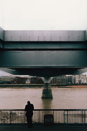Rear view of man standing on bridge over river against sky