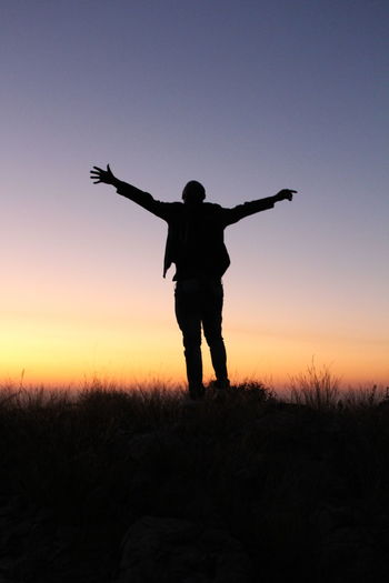Silhouette Man Standing With Arms Outstretched Against Sky