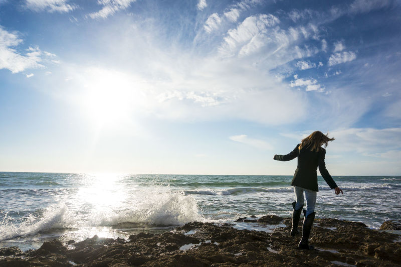 Woman Standing By Sea Against Sky