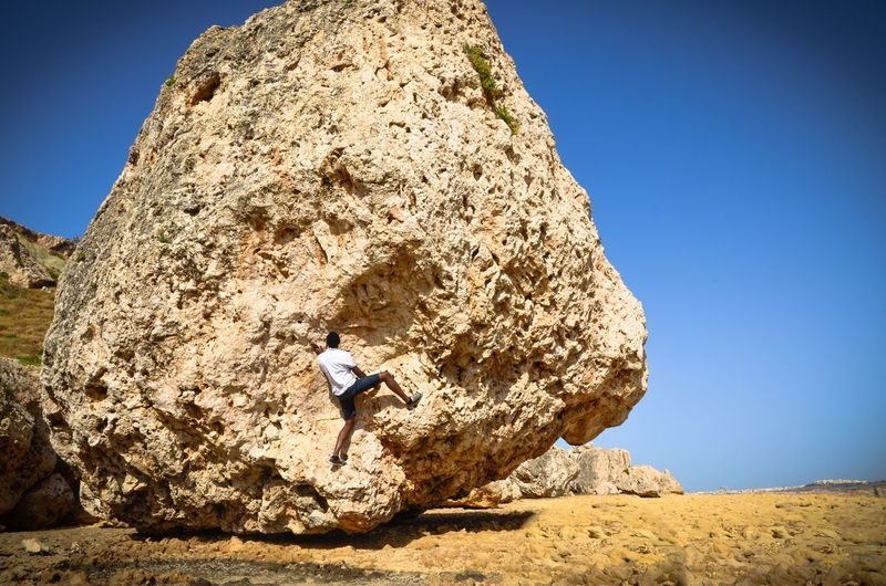 Man climbing rock formation against clear sky