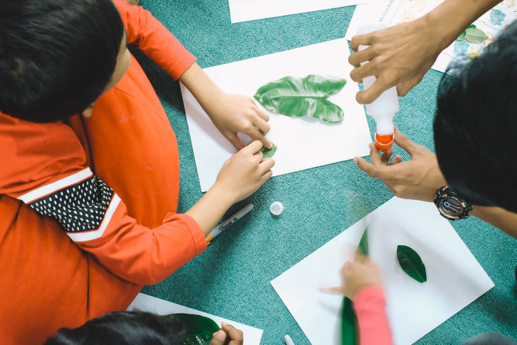 children indoor activity, sticking leaves on paper Adult Adults Only Business Businessman Colleague Day Friendship Group Of People High Angle View Human Body Part Human Hand Indoors  Leaf Occupation Paper People Red Service Small Group Of People Table Teamwork Togetherness Volunteer Resist
