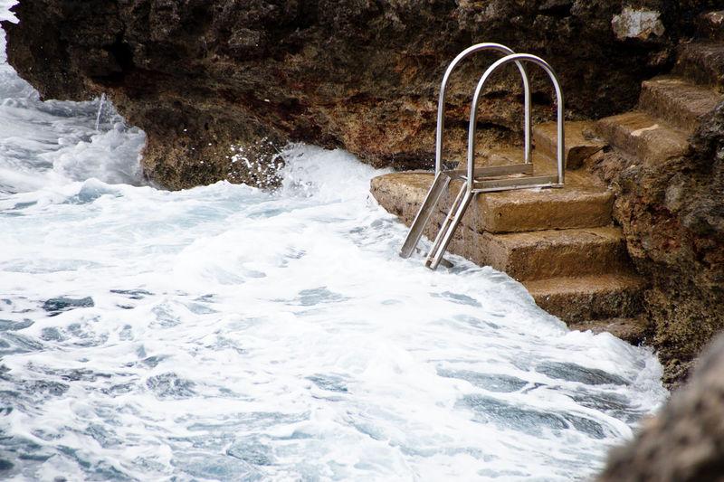 Water flowing through rocks by sea