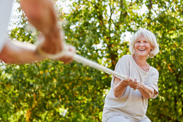 Happy Woman With Friend Pulling Rope Against Trees