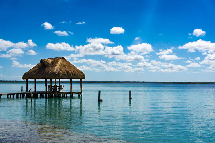 Bacalar Bacalar Lagoon Mexico Relaxing Roof Yúcatan Bacalar Blue Lagoon Mexico Beauty In Nature Blue Day Horizon Horizon Over Water Idyllic Nature No People Outdoors Relaxation Scenics - Nature Sea Thatched Roof Tranquil Scene Tranquility Water Waterfront Yucatan Mexico