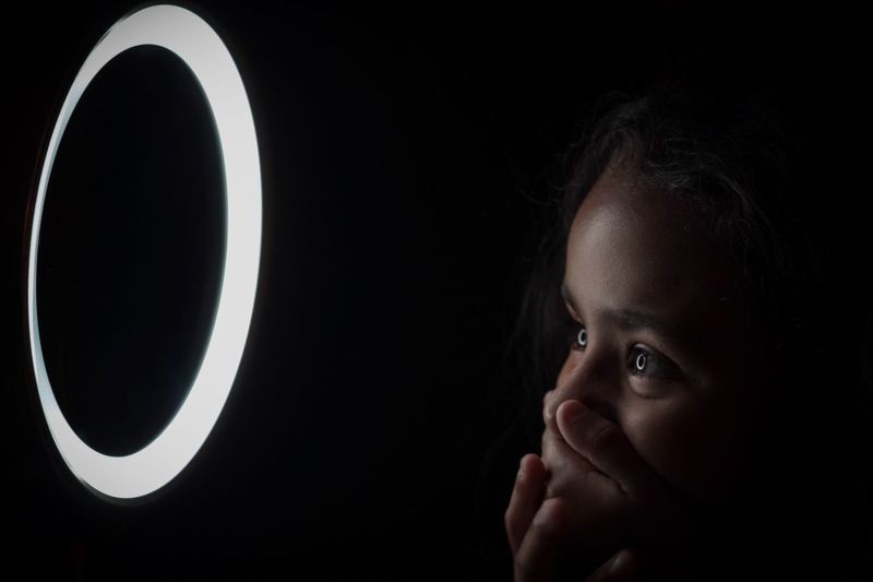Shocked girl looking at illuminated circle against black background
