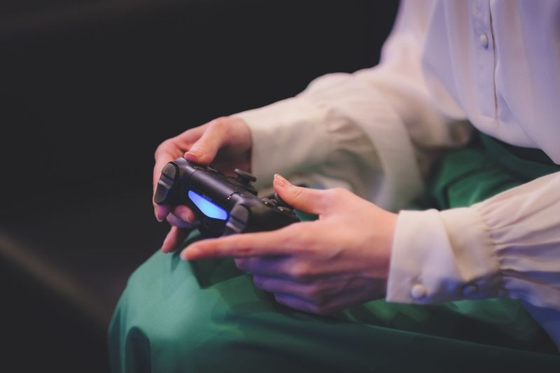 Midsection of woman holding video game controller