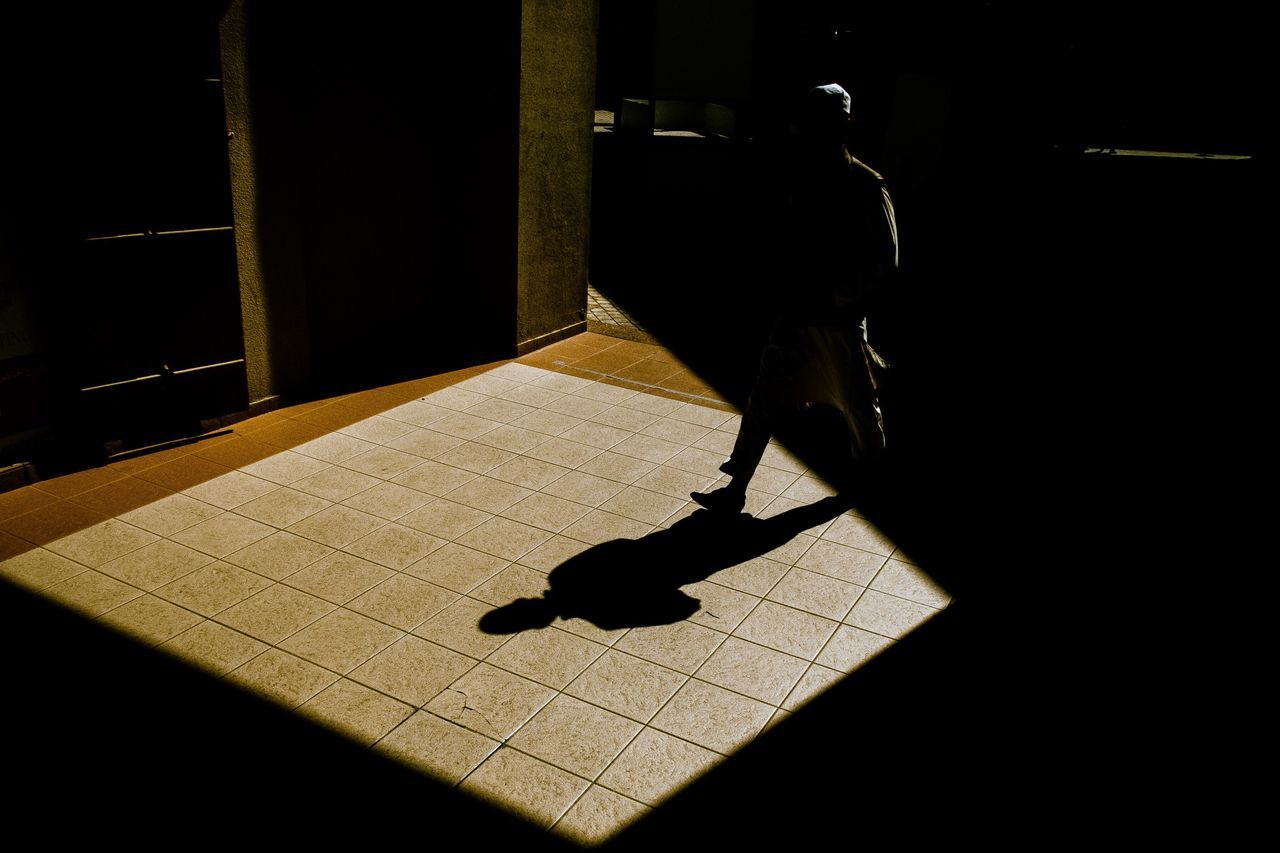 Man shadow on floor during sunny day