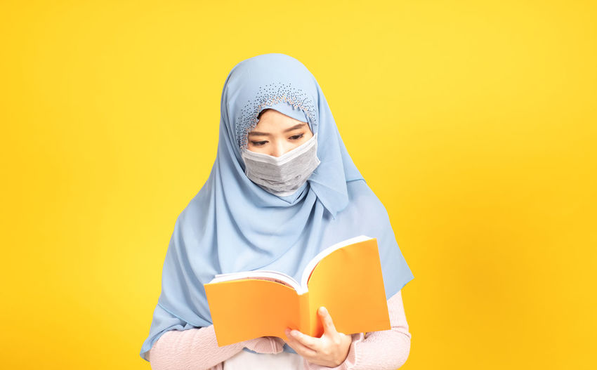 Portrait of teenage girl covering face against yellow background