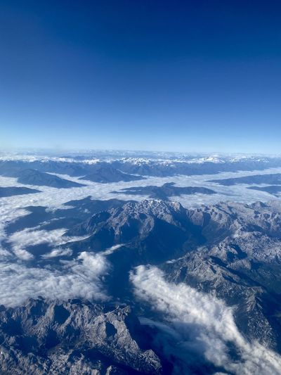 Aerial view of dramatic landscape against blue sky