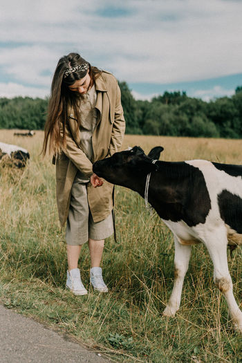 Woman standing by cow on field