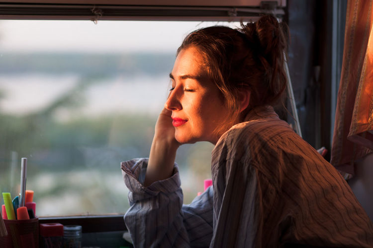 young woman enjoying morning sun next to her window Absorbing Alone Calm Dreaming Home Morning Peace Sunlight Vitamin D Early Enjoying Evening Headshot Indoors  Looking Pajamas Portrait Side View Sitting Summer Sunrise Sunset Window Women Young Adult