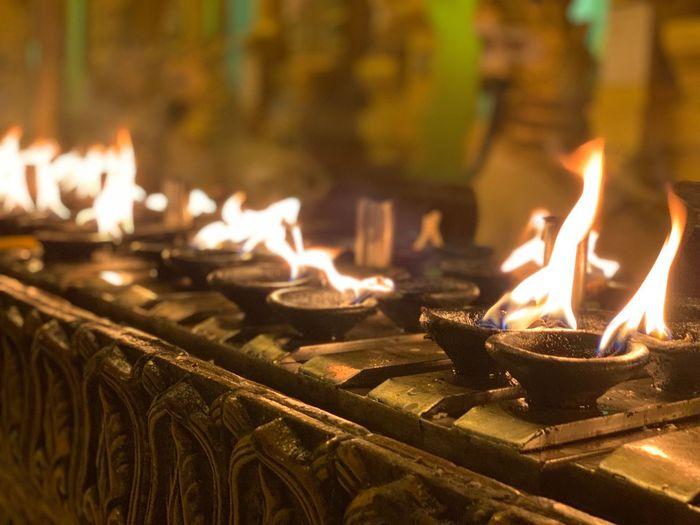 Close-Up Of Burning Diyas At Temple