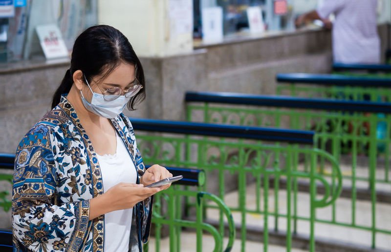 Woman wearing mask using mobile phone while standing outdoors