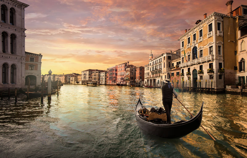 A gondolier is driving his gondola in the grand canal at sunset in Venice, Italy. Nautical Vessel Water Transportation Building Exterior Mode Of Transportation Built Structure Architecture Canal Sky Gondola - Traditional Boat Sunset Waterfront Cloud - Sky Nature Travel Real People City Gondola Outdoors Venice, Italy Sunrise Landscape Urban Skyline Canal Grande Dramatic Sky Cloud Waves Architecture Archival Old Famous Place Rialto Bridge View Tourist Travel Travel Destinations Man Movement Tranquil Scene Way House Vintage History Historical Romance Romantic Honeymoon Beautiful Boat Summer