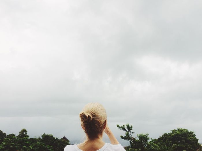Rear view of woman against cloudy sky