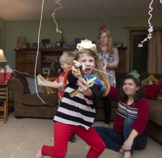 A family celebrates New Years Eve as they enter 2019 at their home with silly string. Child Girls Childhood Females Togetherness Bonding Family Happiness Women Leisure Activity Smiling Group Of People Lifestyles Casual Clothing Boys Positive Emotion Sister Innocence Daughter Party Silly String New Year's Eve New Year's Eve 2019
