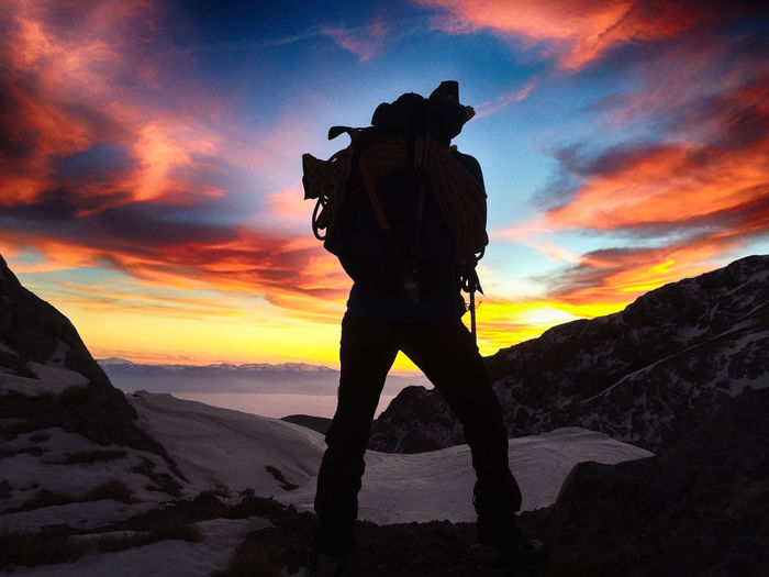 Cowboy Hiking On Snowcapped Mountain Against Sky During Sunset
