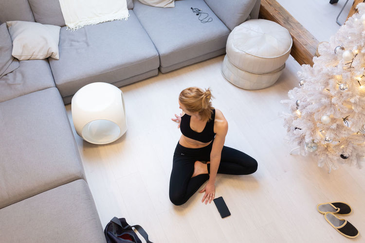 High angle view of woman sitting on sofa at home